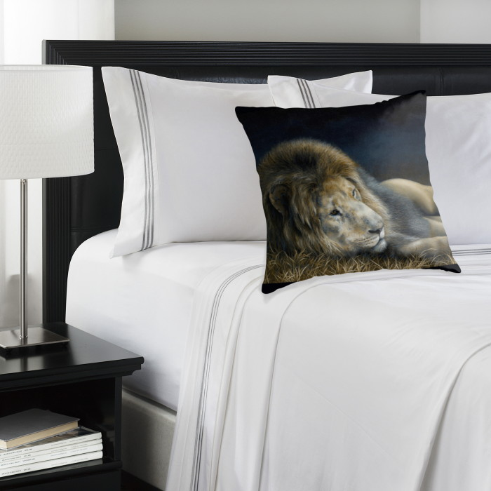 'Africa Dozing - Lion' pillow on a bed. Artwork by Marie-Claire Colyer
